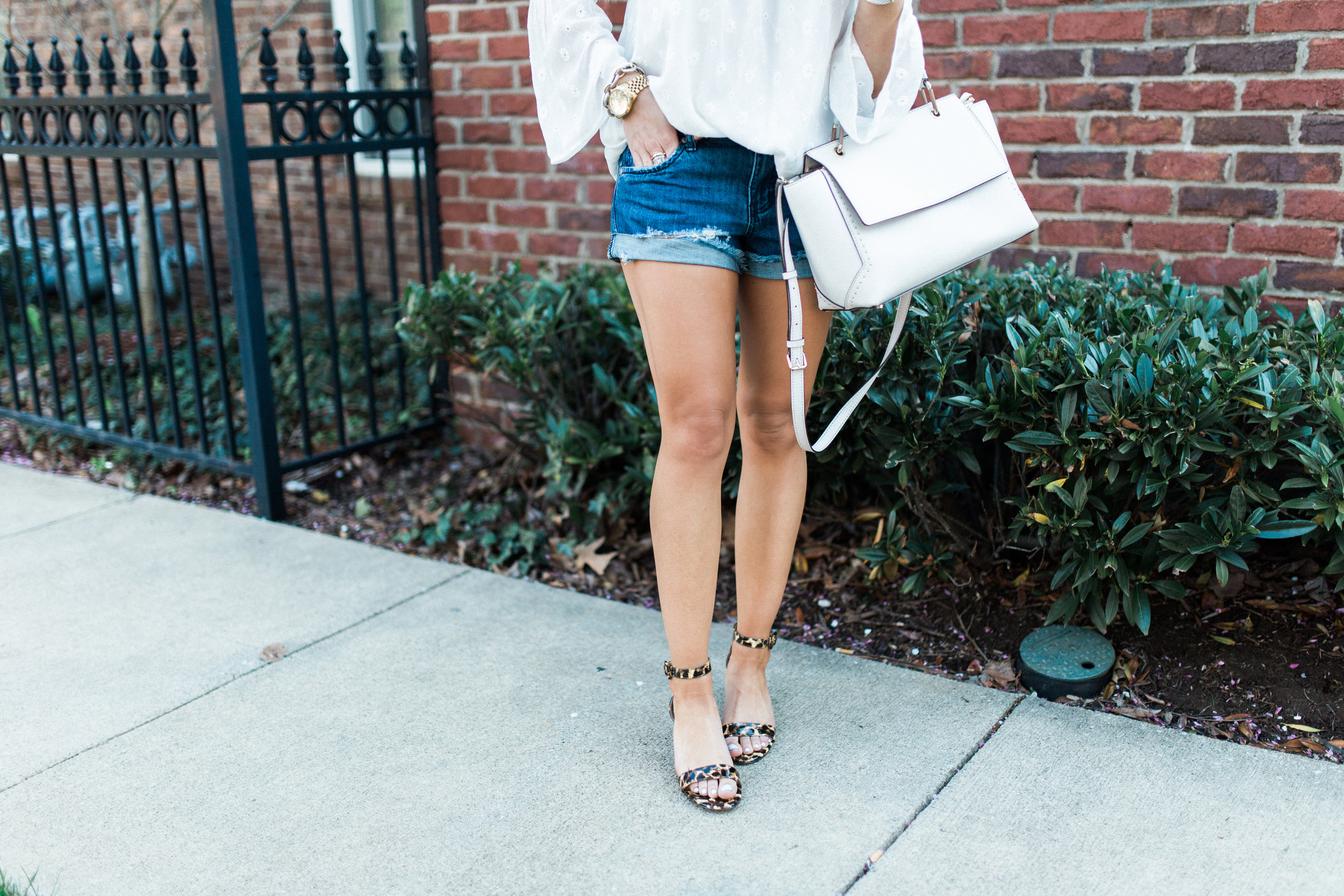 Summer Outfit Idea via Glitter & Gingham // spring outfit inspiration // Ft. Loft White Bell Sleeve Blouse, Denim Shorts, Henri Bendel Bag, Lisi Lerch Tassel Earrings, Leopard Sandals